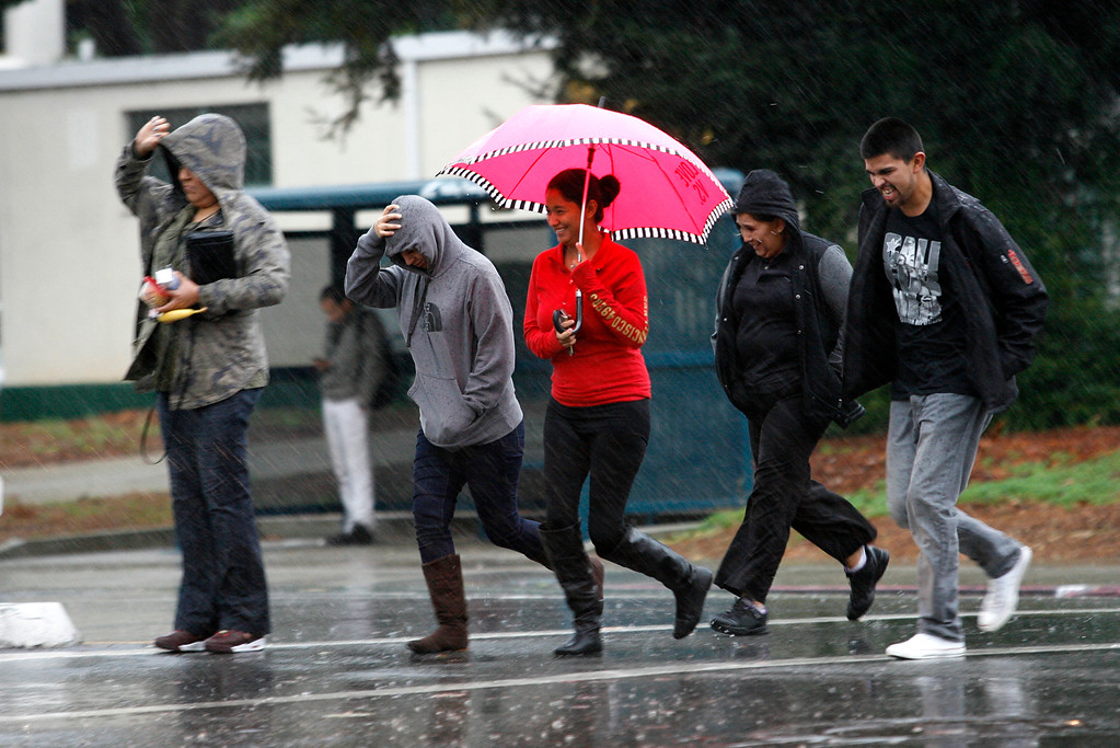 . Pedestrians race across West Hedding Street in a downpour in San Jose, Calif., on Thursday, Dec. 11, 2014.  (Gary Reyes/Bay Area News Group)