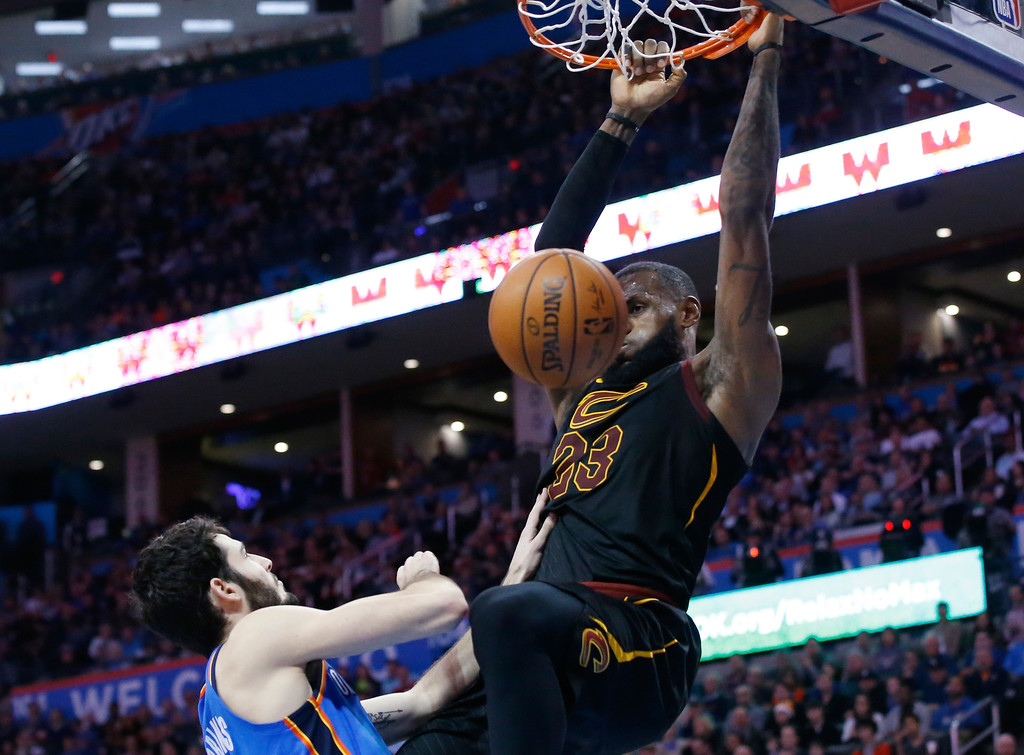 . Cleveland Cavaliers forward LeBron James (23) hangs from the basket after dunking in front of Oklahoma City Thunder guard Alex Abrines left, in the first half of an NBA basketball game in Oklahoma City, Tuesday, Feb. 13, 2018. (AP Photo/Sue Ogrocki)