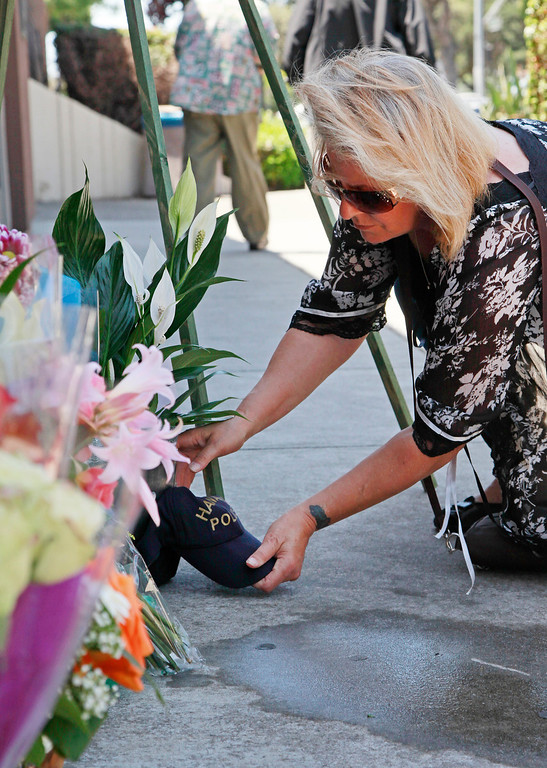 . Tracy Ardito, of Hayward, arranges a plant with a Hayward police hat that she had found by her home this morning outside the Hayward Police Department  in Hayward, Calif., on Wednesday, July 22, 2015.  Ardito said she was praying for the family and friends of fallen Sgt. Scott Lunger and felt her prayers were being heard when she found the hat. She said she lives four blocks from where Lunger was shot early Wednesday morning. (Laura A. Oda/Bay Area News Group)