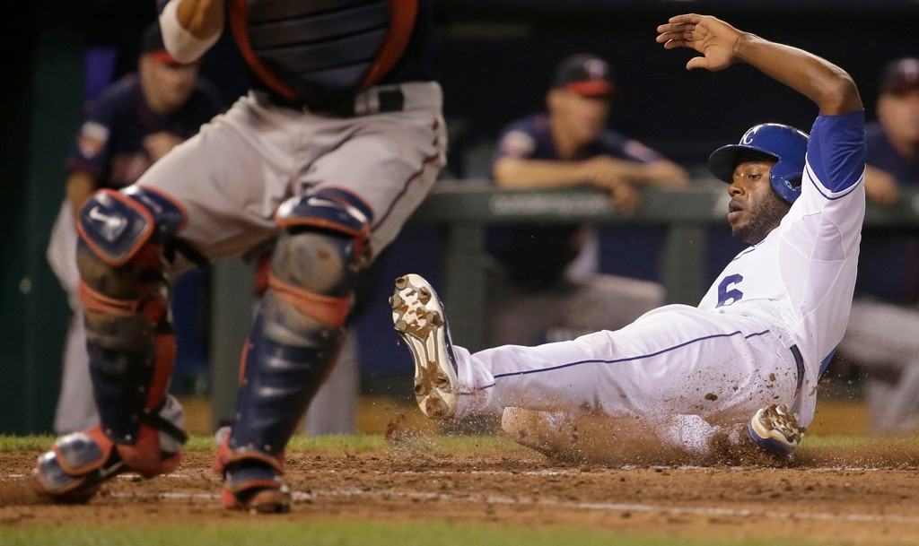 . Kansas City\'s\' Lorenzo Cain slides past Twins catcher Kurt Suzuki as he scores on a single by Christian Colon during the fourth inning. (AP Photo/Charlie Riedel)