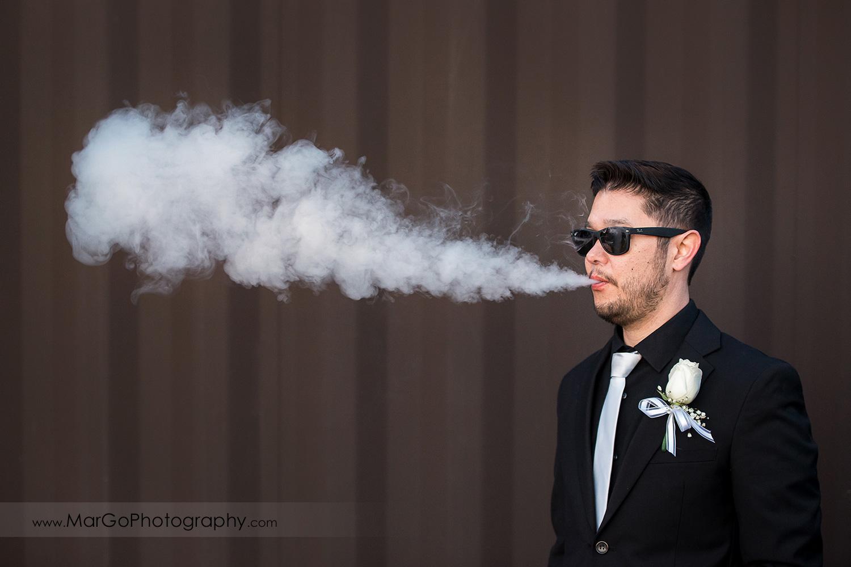 groom smoking cigar at Mt Hamilton GrandView Restaurant in San Jose