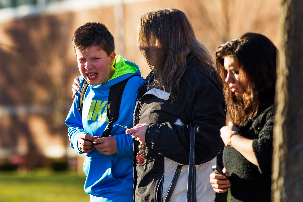 . A boy weeps as he is told what happened after being picked up at Reed Intermediate School following a shooting at Sandy Hook Elementary School in Newtown, Connecticut, December 14, 2012. A heavily armed gunman opened fire on school children and staff at a Connecticut elementary school on Friday, killing at least 26 people, including 18 children, in the latest in a series of shooting rampages that have tormented the United States this year. REUTERS/Lucas Jackson
