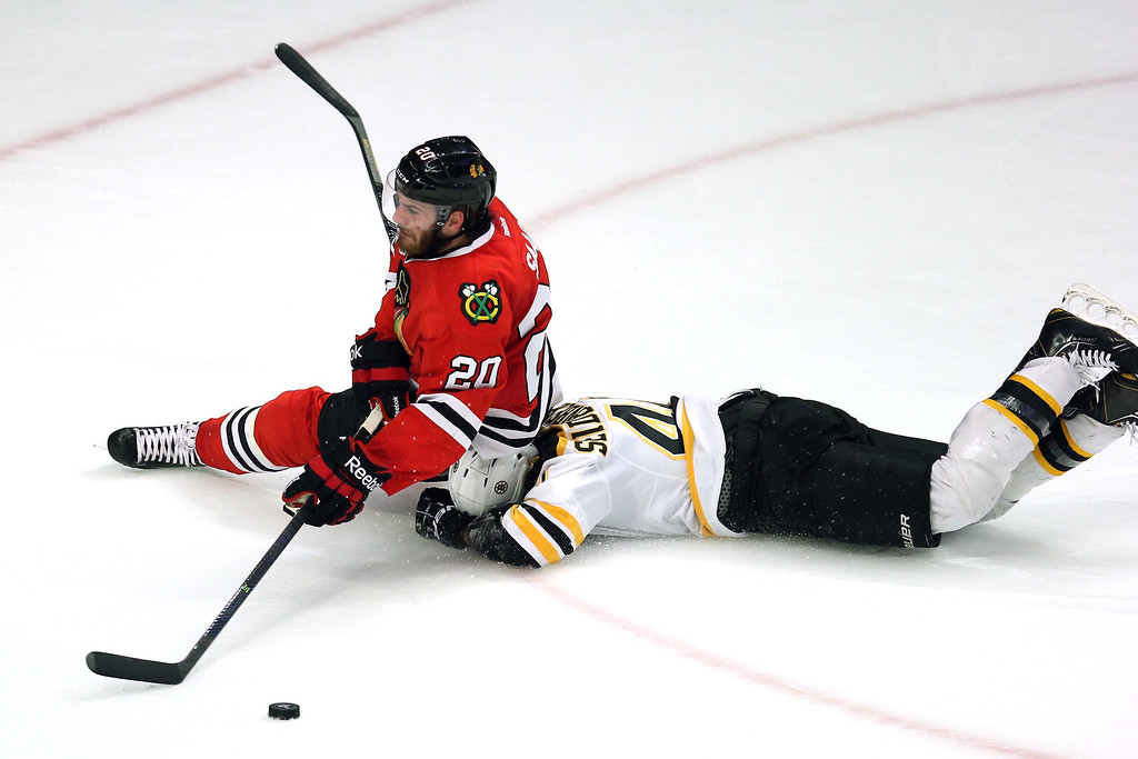 . CHICAGO, IL - JUNE 15:  Brandon Saad #20 of the Chicago Blackhawks falls to the ice on top of Dennis Seidenberg #44 of the Boston Bruins in Game Two of the NHL 2013 Stanley Cup Final at United Center on June 15, 2013 in Chicago, Illinois.  (Photo by Jonathan Daniel/Getty Images)