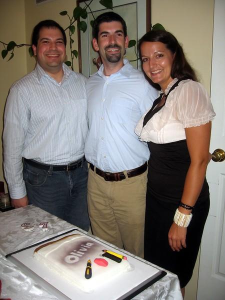 Olivia poses with cake co-creators Craig (left) and David.