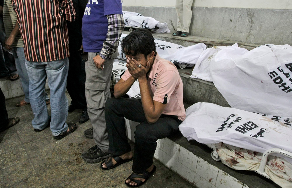 . A Pakistani man, reacts next to the body of a relative who was killed in a bomb blast, at a hospital\'s morgue in Karachi, Pakistan, Sunday, March 3, 2013. Pakistani officials say a bomb blast has killed dozens of people in a neighborhood dominated by Shiite Muslims in the southern city of Karachi. (AP Photo/Fareed Khan)