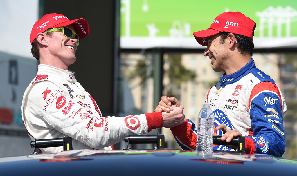 . Toyota Grand Prix of Long Beach winner Scott Dixon, left, and second place finisher Helio Castroneves, share a moment, after seeing each other  for the first time out of their cars, on the victory truck Sunday.  Long Beach  Calif., Sunday,  April,19, 2015.     (Photo by Stephen Carr / Daily Breeze)