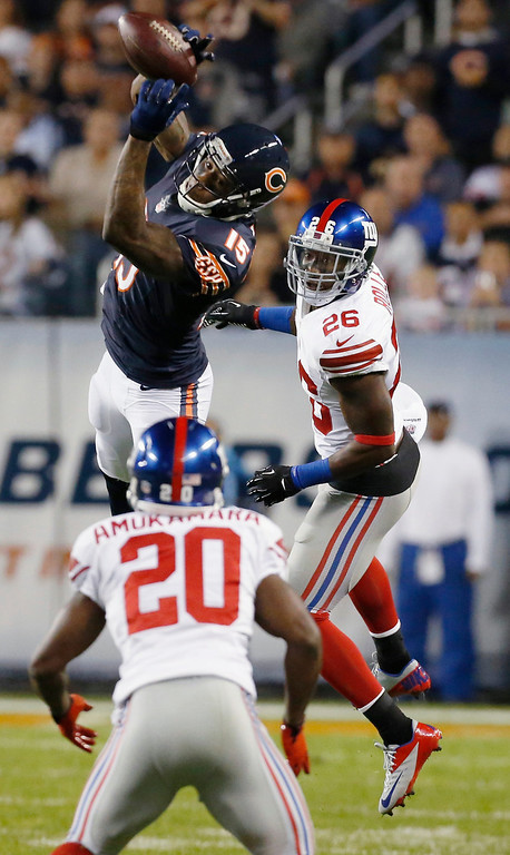 . Chicago Bears wide receiver Brandon Marshall (15) makes a reception against New York Giants cornerback Prince Amukamara (20) and safety Antrel Rolle (26) in the first half of an NFL football game, Thursday, Oct. 10, 2013, in Chicago. (AP Photo/Charles Rex Arbogast)