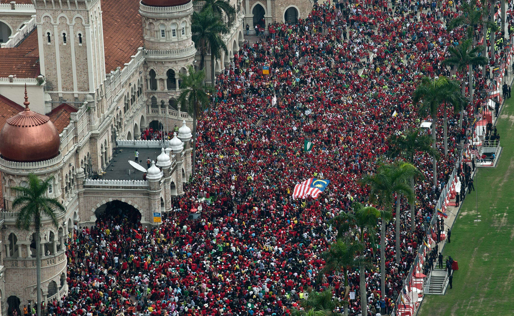 . Protesters carry a Malaysian flag through the crowd during a May Day rally at Independence square in Kuala Lumpur on May 1, 2014. Thousands gathered in Malaysia\'s capital on May 1 to protest against a planned new tax but also took shots at the government\'s prosecution of opposition leader Anwar Ibrahim and handling of missing flight MH370. (MANAN VATSYAYANA/AFP/Getty Images)