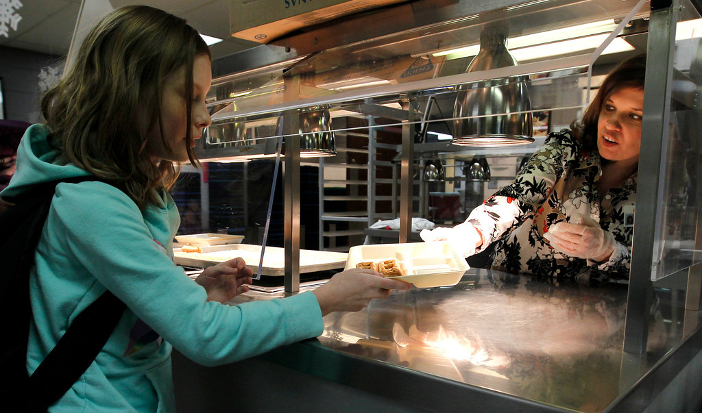 . Naomi Chaves, a student at Oak Mountain Intermediate school, gets some breakfast from assistant principal, Sasha Hood, on Wednesday, Jan. 29, 2014, in Indian Springs, Ala.  (AP Photo/Butch Dill)