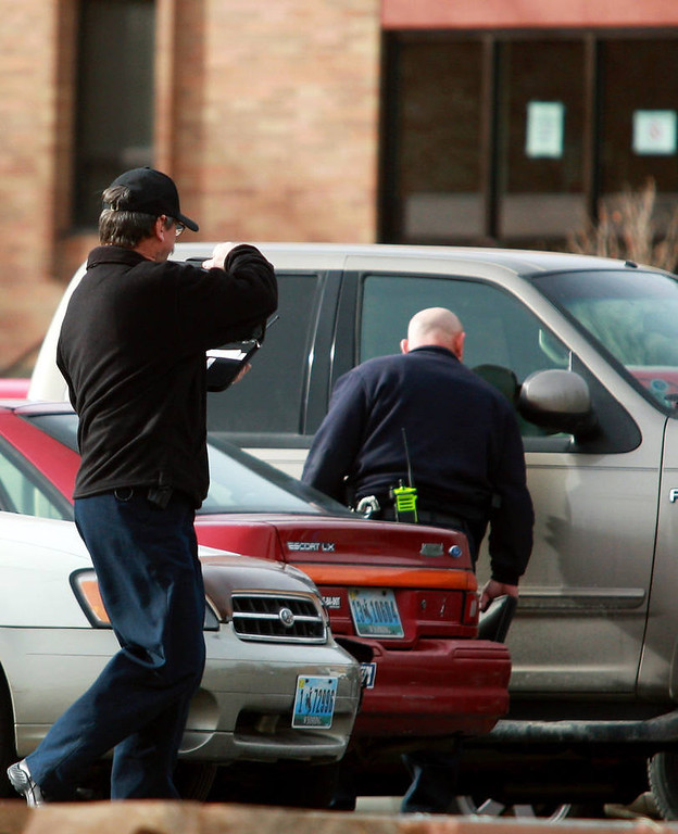 . Casper Police officers check and photograph vehicles at the scene of a reported homicide at Casper College on Friday morning, Nov. 30, 2012, in Casper, Wyo. At least one person was killed and another was wounded Friday in an attack at Casper College, a community college in central Wyoming. It happened around 9 a.m., said school spokesman Rich Fujita.  (AP Photo/Casper Star-Tribune, Alan Rogers)  TRIB.COM