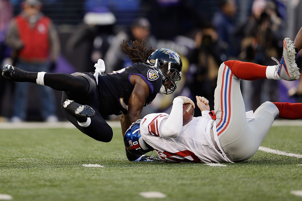. Quarterback Eli Manning #10 of the New York Giants is hit by inside linebacker Dannell Ellerbe #59 of the Baltimore Ravens at M&T Bank Stadium on December 23, 2012 in Baltimore, Maryland.  (Photo by Rob Carr/Getty Images)
