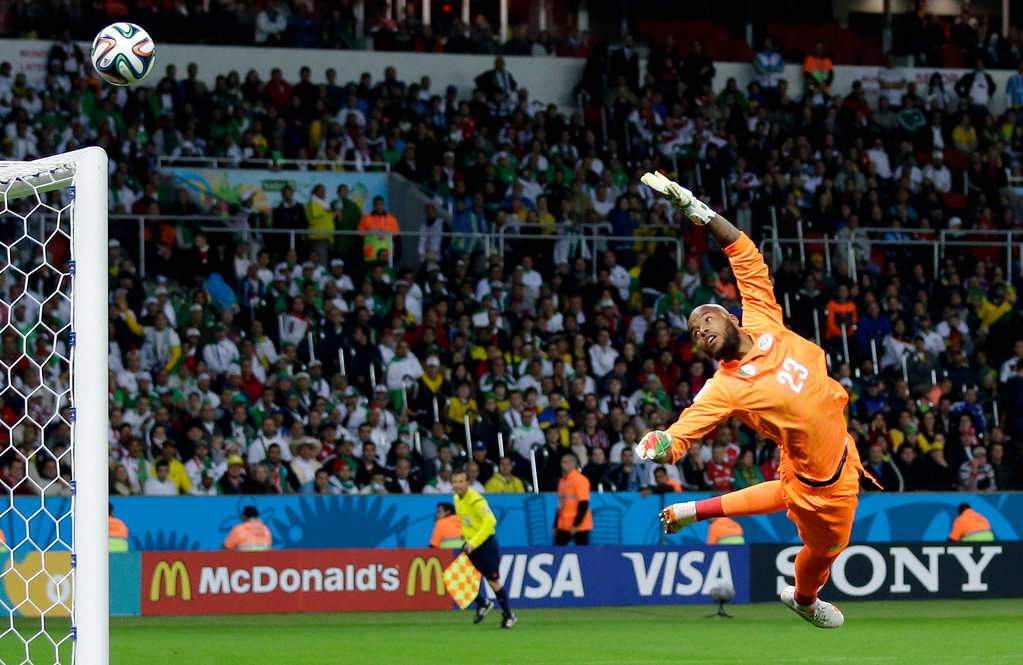 . Algeria\'s goalkeeper Rais MíBolhi dives for the ball during the World Cup round of 16 soccer match between Germany and Algeria at the Estadio Beira-Rio in Porto Alegre, Brazil, Monday, June 30, 2014. (AP Photo/Sergei Grits)