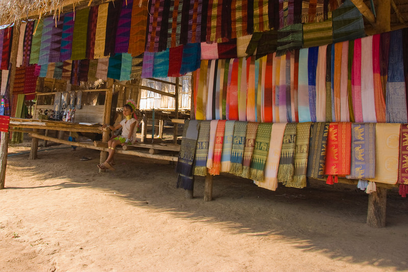 Kayan girl sitting next to hung fabric - Chiang Mai, Thailand