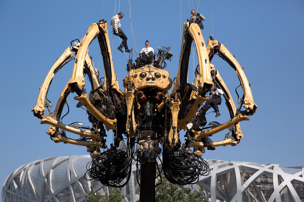 ". Performers rappel down to the French production company La Machine\'s mechanical spider also known as ""La Princesse\"" during a show held in front of the Bird\'s Nest Stadium in Beijing, China, Friday, Oct. 17, 2014. A series of performances over three days will mark the climax of celebrations for the 50th anniversary of Sino-French diplomatic relations on Sunday, Oct 19.  (AP Photo/Ng Han Guan)"