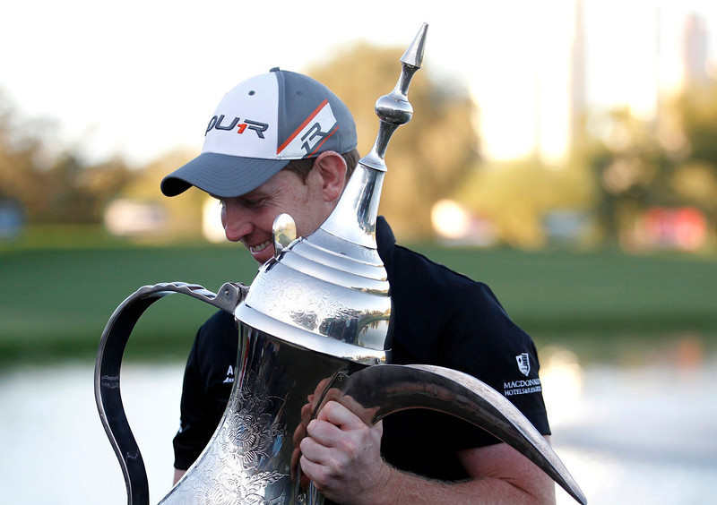 . Stephen Gallacher of Scotland poses with the trophy at the 18th green after the fourth and final round of the Dubai Desert Classic at the Emirates Golf Club on February 3, 2013. Gallacher won the Dubai Desert Classic on Sunday with a final-round 71 for a total of 266 in the European Tour golf event. REUTERS/Jumana El Heloueh