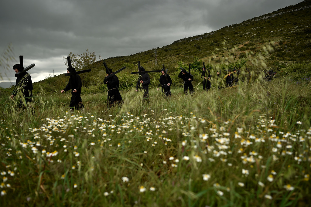 . Devotes walk through a field holding their crosses during a march of the \'\'Romeros de Lumbier\'\' near to the small village of Lumbier, northern Spain, Sunday, May 22, 2016. Every year devotees march from their small town to a Trinity Chapel in the top of the hill where they receive a blessing. (AP Photo/Alvaro Barrientos)