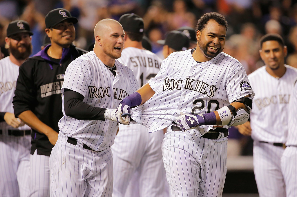 . DENVER, CO - SEPTEMBER 18:  Wilin Rosario #20 of the Colorado Rockies is congratulated by Brandon Barnes #1 of the Colorado Rockies after hitting the game winning walk off two run home run off of Addison Reed #43 of the Arizona Diamondbacks at Coors Field on September 18, 2014 in Denver, Colorado. The Rockies defeated the Diamondbacks 7-6.  (Photo by Doug Pensinger/Getty Images)