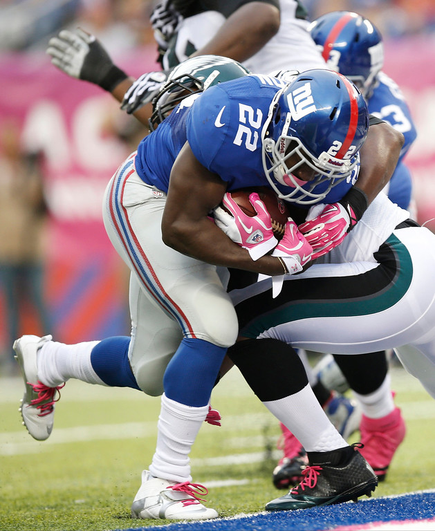 . New York Giants\' David Wilson (22) breaks a tackle by Philadelphia Eagles\' DeMeco Ryans for a touchdown during the first half of an NFL football game Sunday, Oct. 6, 2013, in East Rutherford, N.J.  (AP Photo/Kathy Willens)