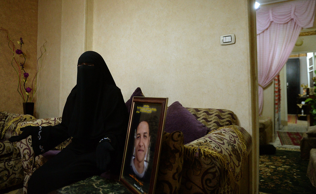 ". A fully-veiled Muslim woman, identified as Um Moaz, sits on August 22, 2013 at home in Cairo next to a picture of her son who was shot dead during the ""Friday of Rage\""on January 28, 2011, at the height of the revolution against Egypt\'s deposed president Hosni Mubarak. Um Moaz said she feels that the \""revolution\"" as well as her son and all the others who were killed were betrayed following news that the former president was expected to leave the prison following a court order for his conditional release pending trial. The ex-president, who could walk out of prison on August 22, will immediately be placed under house arrest.  MARWAN NAAMANI/AFP/Getty Images"