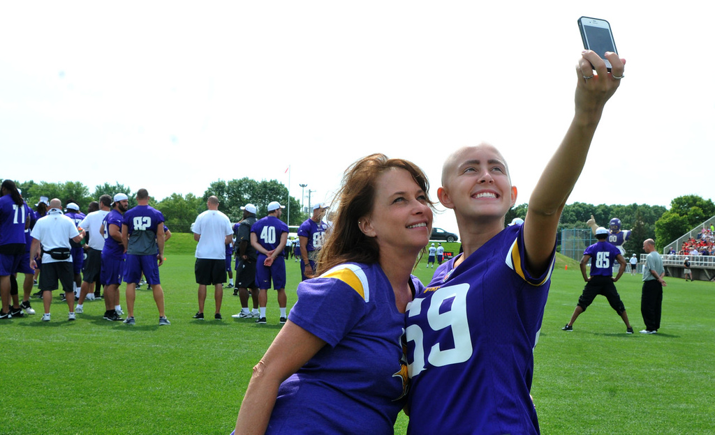 """. Charlotte Fournier, left, and her daughter, Taylor Fournier, of Andover shoot \""""selfies\"""" on the Vikings practice field as the team works out behind them.   (Pioneer Press: John Doman)"""