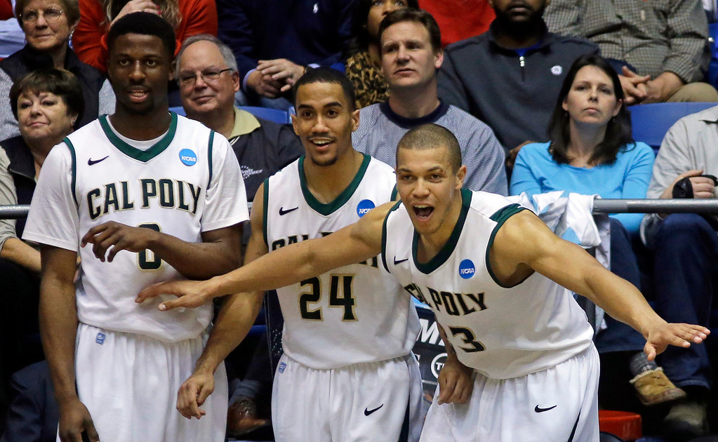 . Cal Poly players, from left to right, Dave Nwaba, Jamal Johnson and Chris Eversley celebrate on the bench in the closing seconds of their 81-69 win over Texas Southern in a first-round game of the NCAA college basketball tournament, Wednesday, March 19, 2014, in Dayton, Ohio. (AP Photo/Al Behrman)