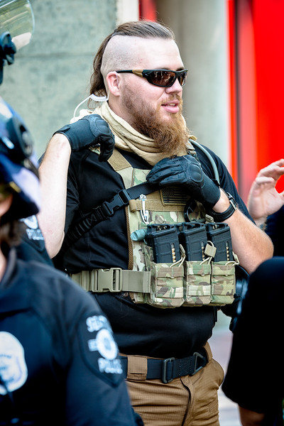 """A member of the far right, with several ammo clips attached to his pack, talks with others at the """"Liberty or Death"""" rally at Seattle City Hall."""