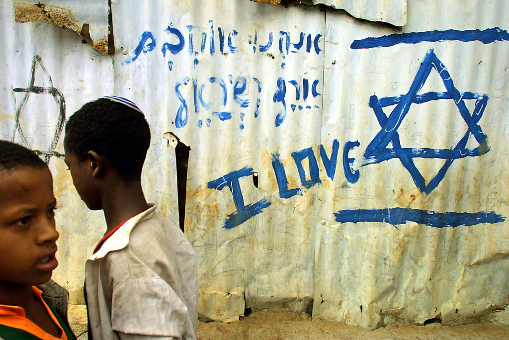 """. ADDIS ABABA, ETHIOPIA - MARCH 14:  Jewish Ethiopian students walk to their classes at the Beta Israel School March 14, 2003 in Addis Ababa, Ethiopia. After airlifting more than 22,000 Ethiopian Jews in 1984, and 1991, and satisfied that all qualified Jews had left Ethiopia in the airlifts, the Israeli government closed down its offices in Addis Ababa. However, in recent years, those Jews who were left behind have moved from their villages to Addis Ababa and are waiting for the Israeli government to accept them under the \""""Law of Return.\"""" Nearly 17,000 Ethiopian Jews awaiting aliyah, or emigration to Israel, live in Addis Ababa and the northern city of Gondar. For reasons that include a limited paper trail authenticating their Jewish identity, conversions to Christianity by grandparents, or a reluctance on the part of Israel to accept more Ethiopian refugees, the Ethiopian Jews have lingered around in compounds waiting indefinitely.  (Photo by Natalie Behring-Chisholm/Getty Images)"""