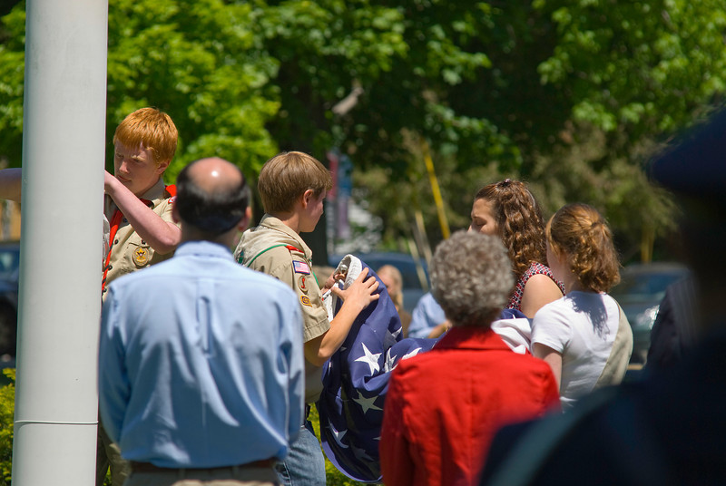 Folding the Flag - After lowering the flag in the town center, local Boy Scouts fold the flag for a veteran's family.