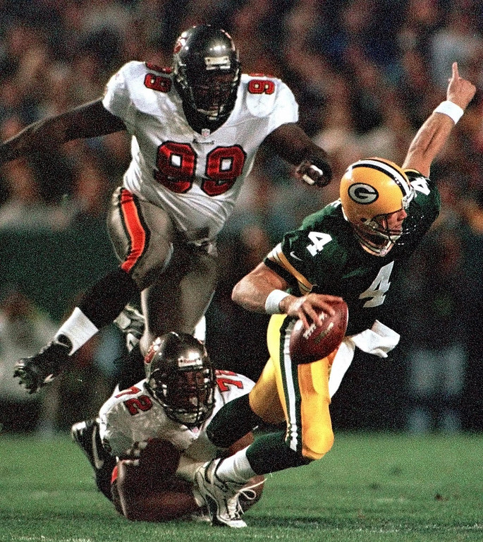 . Green Bay Packers quarterback Brett Favre (4) gets away from Tampa Bay Buccaneers Chidi Ahanotu (72) and Warren Sapp (99) to complete a pass in the first quarter Sunday night, Oct. 10, 1999, in Green Bay, Wis. (AP Photo/Andy Manis)