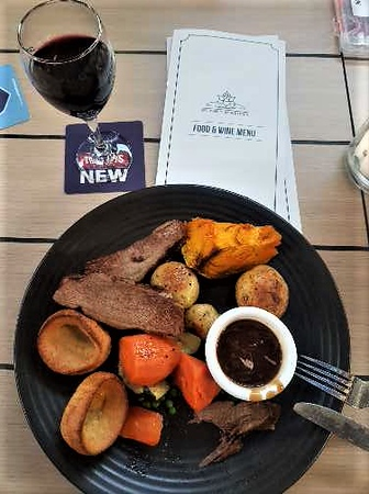 Plate with roast beef, veggies, and Yorkshire puddings on a table with a glass of red wine. Stumbling upon good food is part of the Sunday adventure