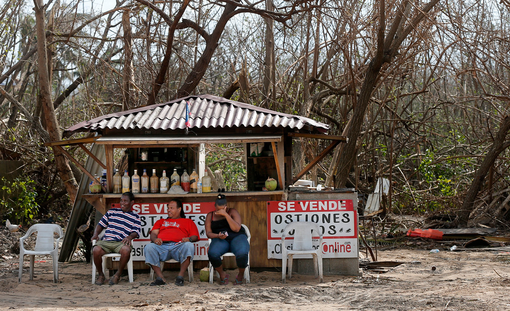 . Vendors with no customers sit in front of destroyed trees, in the aftermath of Hurricane Maria in Loiza, Puerto Rico, Sunday, Sept. 24, 2017. Federal aid is racing to stem a growing humanitarian crisis in towns left without fresh water, fuel, electricity or phone service by the hurricane. (AP Photo/Gerald Herbert)