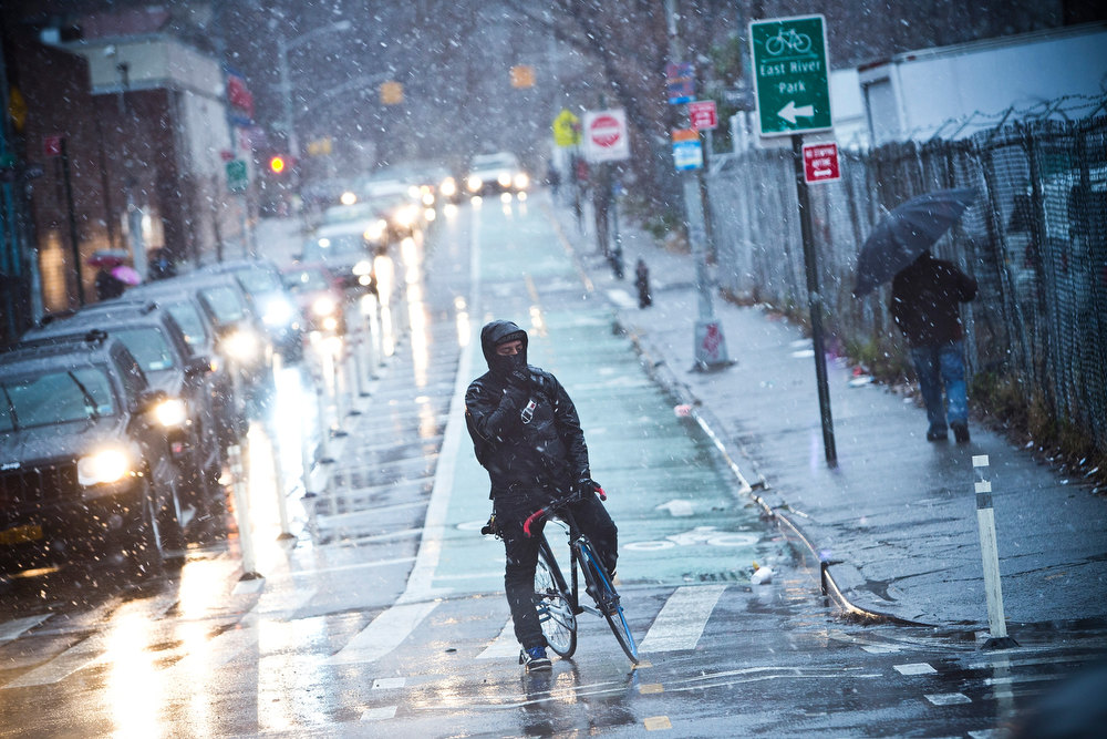 Description of . A cyclist waits to cross the street while a winter snow storm hits the region on December 26, 2012 in New York City. Snow, mixed with and changing to rain, is expected to hit the New York City area this afternoon into the evening. (Photo by Andrew Burton/Getty Images)