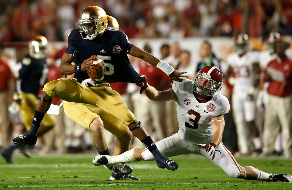 . Notre Dame Fighting Irish quarterback Everett Golson is grabbed by Alabama Crimson Tide defensive back Vinnie Sunseri during the second quarter of their NCAA BCS National Championship college football game in Miami, Florida, January 7, 2013. REUTERS/Mike Segar