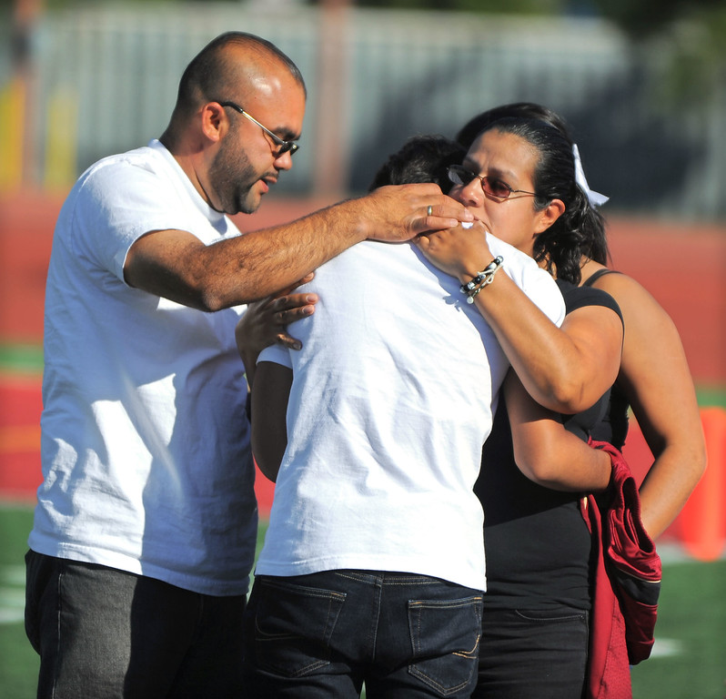 . Dodi Soza\'s brother Derrick, center, is consoled by his father, Eduardo, and mother, Luz, following him in a brief tribute to Dodi during a Downey High JV football game against Warren in Downey, CA on Thursday, October 17, 2013. Dodi Soza collapsed on the field after scoring a touchdown and died two days later on Saturday. On the first offensive play of Thursdays game, quarterback Kiefer Enslin carried Soza\'s jersey onto the field and set it on the turf where Soza normally played. Soza\'s brother, Derrick, then went onto the field to retrieve the jersey and brought it to family members.  (Photo by Scott Varley, Daily Breeze)