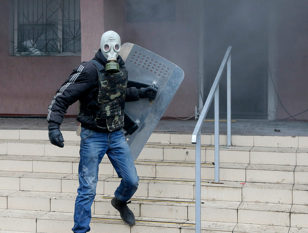 . A pro-Russian wearing a gas mask storms a police station in Horlivka, eastern Ukraine, Monday, April 14, 2014. Ukraine\'s acting President Oleksandr Turchynov on Monday called for the deployment of United Nations peacekeeping troops in the east of the country, where pro-Russian insurgents have occupied buildings in nearly 10 cities. (AP Photo/Efrem Lukatsky)