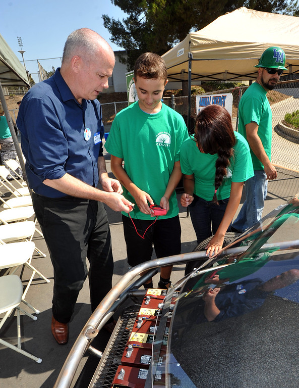 . Michael Mack, left, shows students, Andrew Valdivia, center, and Andrea Motts, the new Electric Auto Shop kit vehicle at La Mirada High School in La Mirada, CA on Tuesday September 10, 2013. The vehicle, which is highway ready, will be assembled and disassembled for the next year\'s class. (San Gabriel Valley Tribune/Staff Photo by Keith Durflinger)