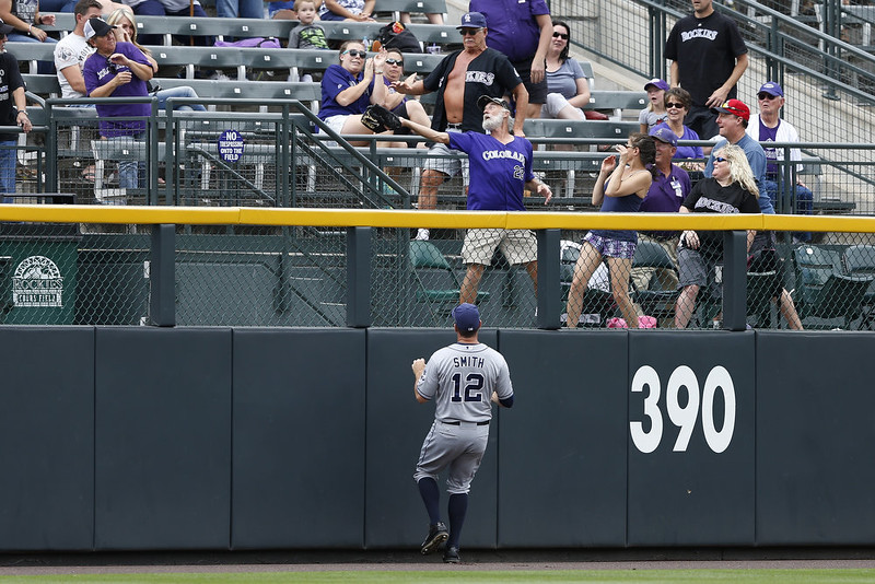 . Seth Smith #12 of the San Diego Padres looks up as a fan catches a three-run home run ball off the bat of Jackson Williamsof the Colorado Rockies in the second inning of the game at Coors Field on September 7, 2014 in Denver, Colorado. (Photo by Joe Robbins/Getty Images)