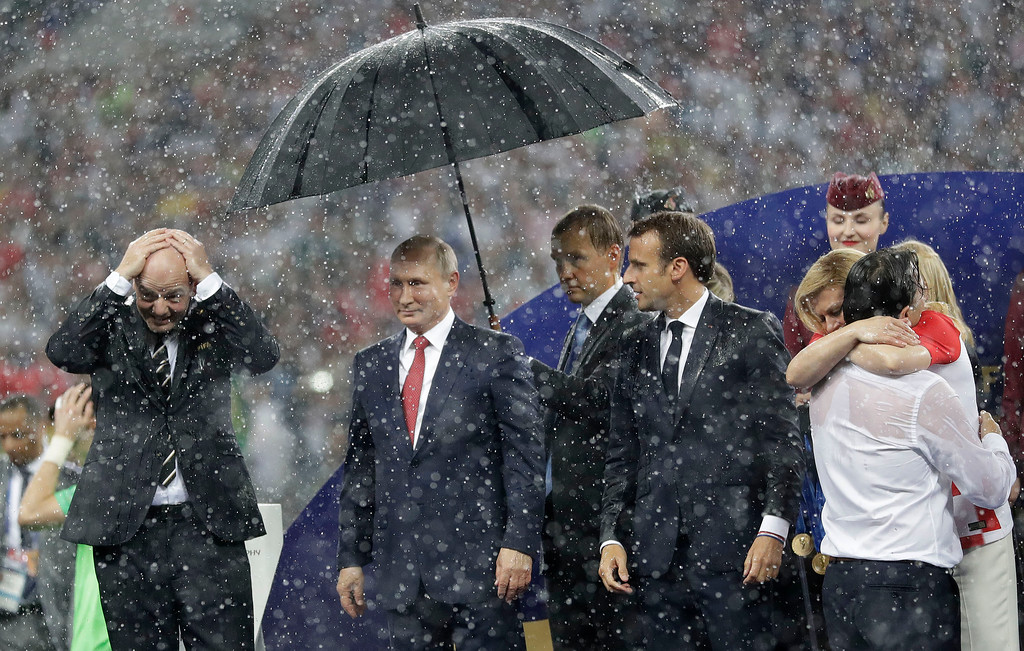 . FIFA President Gianni Infantino, left, gestures as Russian President Vladimir Putin stands underneath an umbrella as Croatian President Kolinda Grabar-Kitarovic greets Croatia head coach Zlatko Dalic after the final match between France and Croatia at the 2018 soccer World Cup in the Luzhniki Stadium in Moscow, Russia, Sunday, July 15, 2018. France won the final 4-2. (AP Photo/Matthias Schrader)