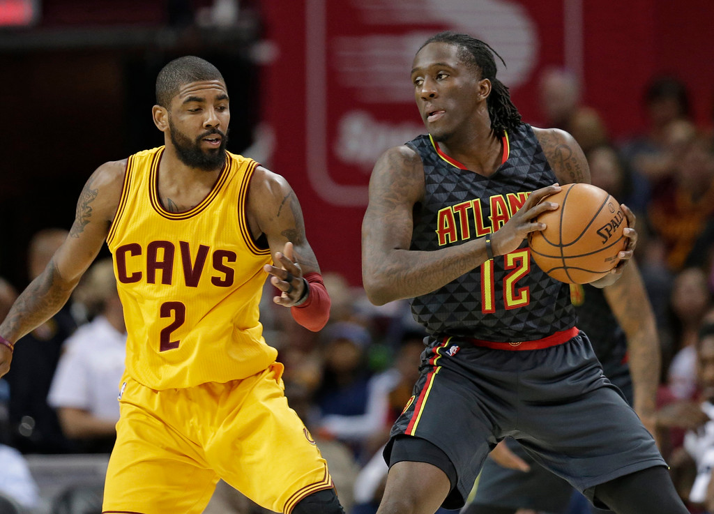 . Atlanta Hawks\' Taurean Prince (12) drives past Cleveland Cavaliers\' Kyrie Irving (2) in the first half of an NBA basketball game, Friday, April 7, 2017, in Cleveland. (AP Photo/Tony Dejak)