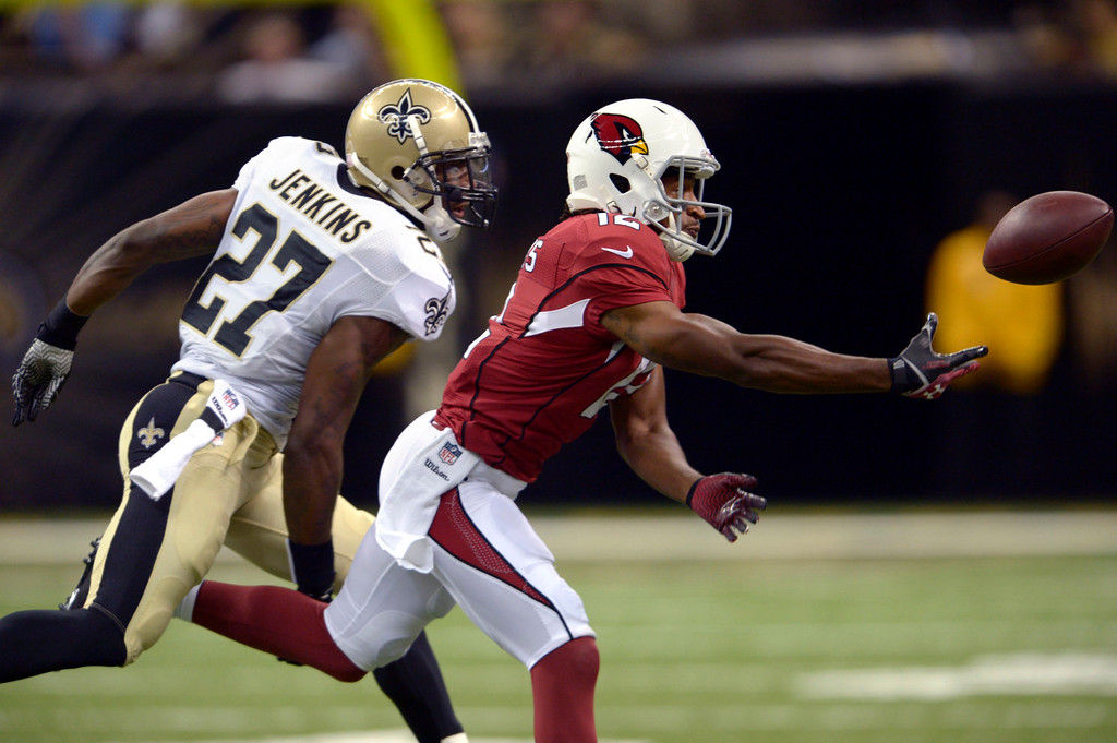 . Arizona Cardinals wide receiver Andre Roberts (12) tries to pull in a pass in front of New Orleans Saints free safety Malcolm Jenkins (27) in the first half of an NFL football game in New Orleans, Sunday, Sept. 22, 2013. (AP Photo/Bill Feig)