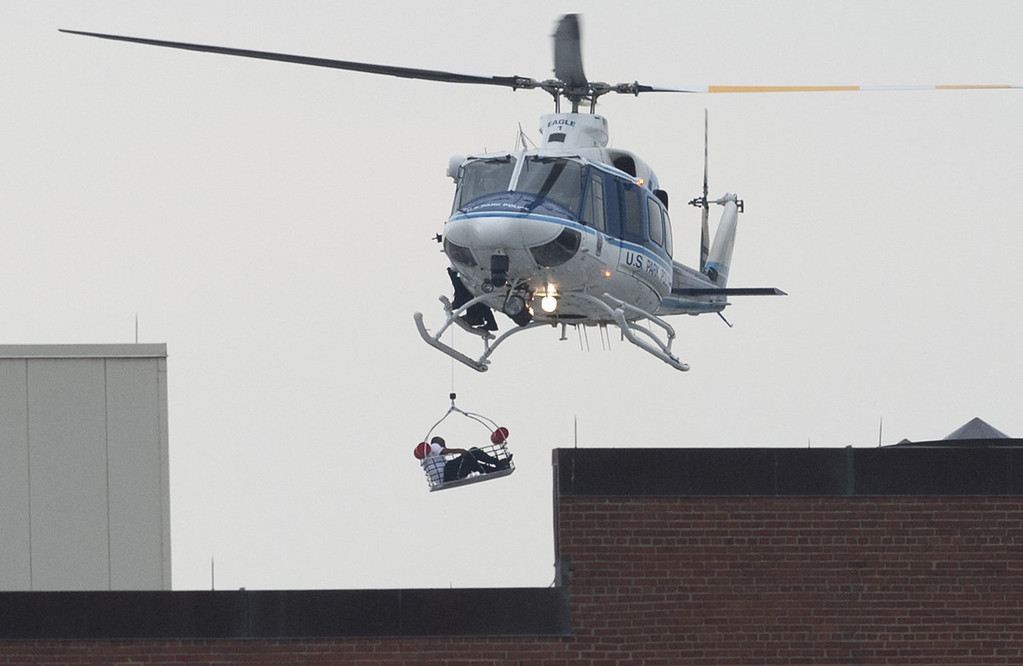 """. A helicopter lifts a person off the roof as police respond to the report of a shooting at the Navy Yard in Washington, Dc on September 16, 2013.  Departures have been halted at Washington\'s Reagan National Airport due to a shooting at the US Navy Yard, an official said Monday. Chris Paolino, a spokesman for the airport, said inbound aircraft are still landing and that the airport remains open to passengers. \""""We can confirm that the FAA (Federal Aviation Administration) has halted aircraft departures from Reagan National due to an active law enforcement incident at the Washington Navy Yard,\"""" Paolino told AFP via email. Several people have been wounded in the shooting at the nearby US Navy Yard in Washington, authorities said. The Navy said at least three shots were fired at 8:20 am (1320 GMT) in the headquarters building of the Naval Sea Systems Command.   SAUL LOEB/AFP/Getty Images"""