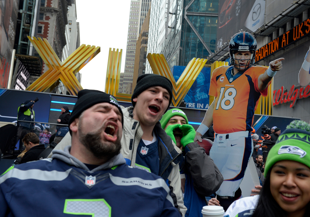. A  cut out of Denver Broncos quarterback Payton Manning is hoisted over cheering Seattle Seahawks visiting  Times Square in New York, NY January 31, 2014. The NFL has transformed 13 blocks of Broadway into a center for Super Bowl activity before Sundays Super Bowl between the Denver Broncos and Seattle Seahawks. (Photo By Craig F. Walker / The Denver Post)