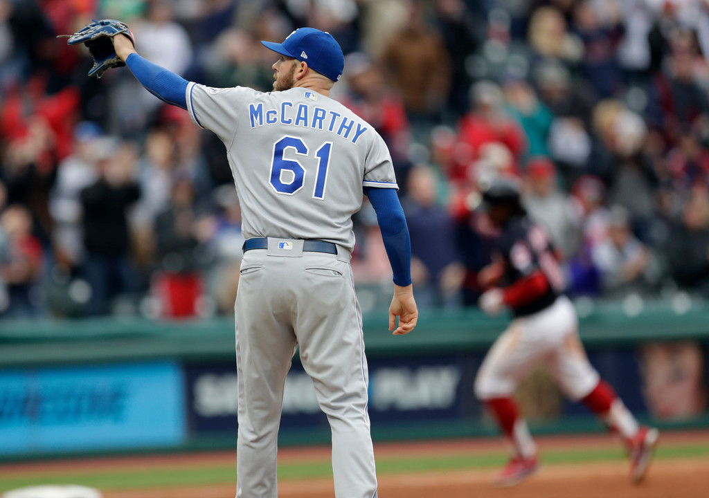 . Kansas City Royals\' Kevin McCarthy, left, waits for Cleveland Indians\' Francisco Lindor to run the bases on a solo home run during the seventh inning of a baseball game Saturday, May 12, 2018, in Cleveland. The Indians won 6-2. (AP Photo/Tony Dejak)
