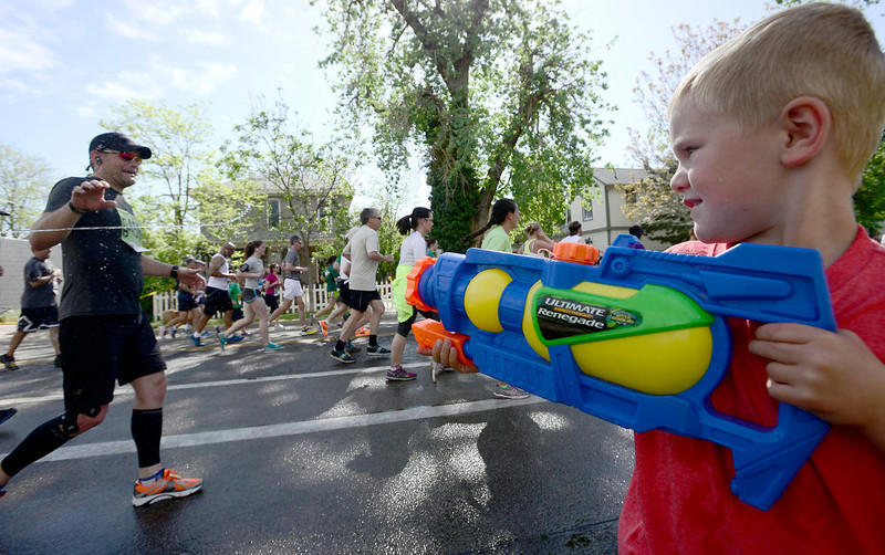 . Aiden Warrow (right), 4, squirts Christopher Tamisiea (left) as he passes by during the Bolder Boulder in Boulder, Colorado May 27, 2014.  DAILY CAMERA/ Mark Leffingwell