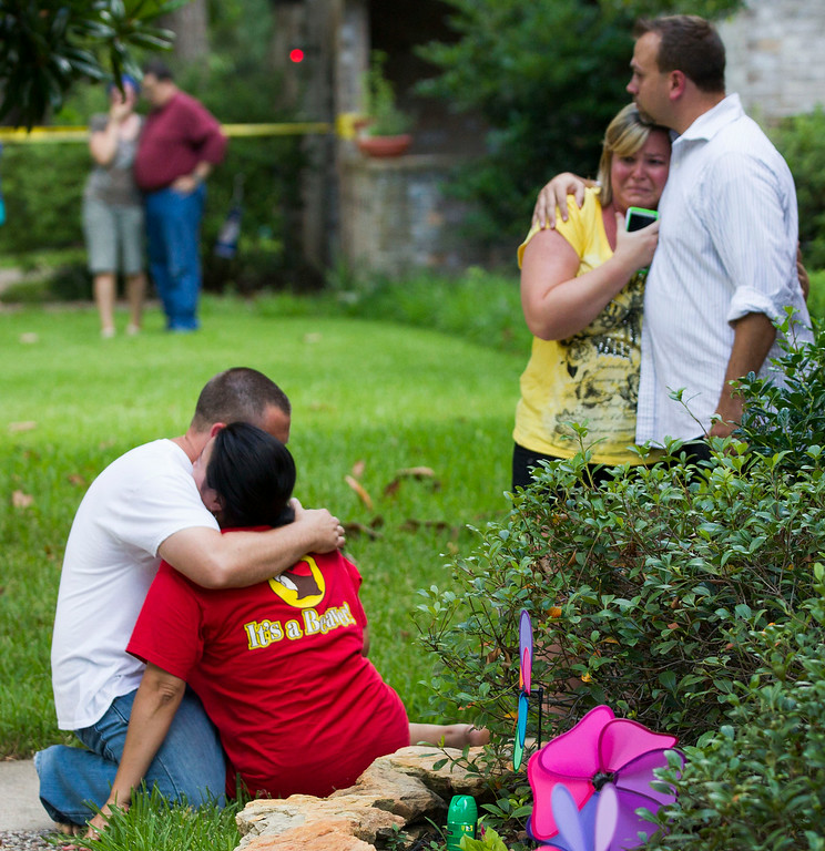 . Neighbors embrace each other following a shooting Wednesday, July 9, 2014, in Spring, Texas. Deputies have cornered a man suspected in a shooting at a suburban Houston home that resulted in multiple fatalities. (AP Photo/Houston Chronicle, Brett Coomer)