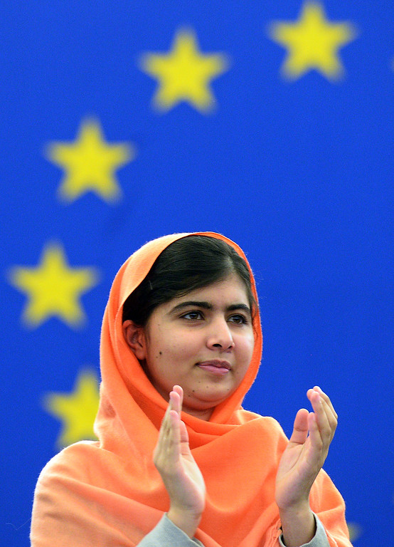 . In this photograph taken on November 20, 2013 Malala Yousafzai, a Pakistani student who was shot in the head by the Pakistani Taliban applauds a speech after being awarded with the Sakharov Prize for Freedom of Thought at the European Parliament in Strasbourg, eastern France.  The Nobel Peace Prize went October 10, 2014 to 17-year-old Pakistani Malala Yousafzai and India\'s Kailash Satyarthi for their work promoting children\'s rights.  AFP PHOTO/ PATRICK  HERTZOG/AFP/Getty Images