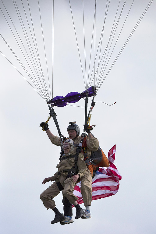 """. US war veteran Jim \""""Pee Wee\"""" Martin (L), 93, prepares to land with a parachute on June 5, 2014 over Carentan, where he landed 70 years ago, when he was a paratrooper. The D-Day ceremonies on June 6 this year mark the 70th anniversary since the launch of \'Operation Overlord\', a vast military operation by Allied forces in Normandy, which turned the tide of World War II, eventually leading to the liberation of occupied France and the end of the war against Nazi Germany.  AFP PHOTO / JOEL SAGET/AFP/Getty Images"""