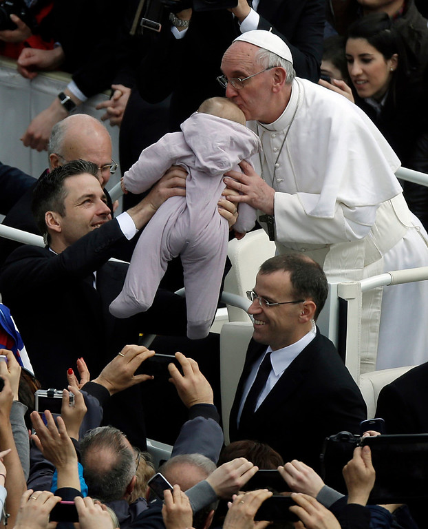 . Pope Francis kisses a baby after celebrating his first Easter Mass in St. Peter\'s Square at the Vatican, Sunday, March 31, 2013. Pope Francis celebrated his first Easter Sunday Mass as pontiff in St. Peter\'s Square, packed by joyous pilgrims, tourists and Romans and bedecked by spring flowers. Wearing cream-colored vestments, Francis strode onto the esplanade in front of St. Peter\'s Basilica and took his place at an altar set up under a white canopy. (AP Photo/Gregorio Borgia)