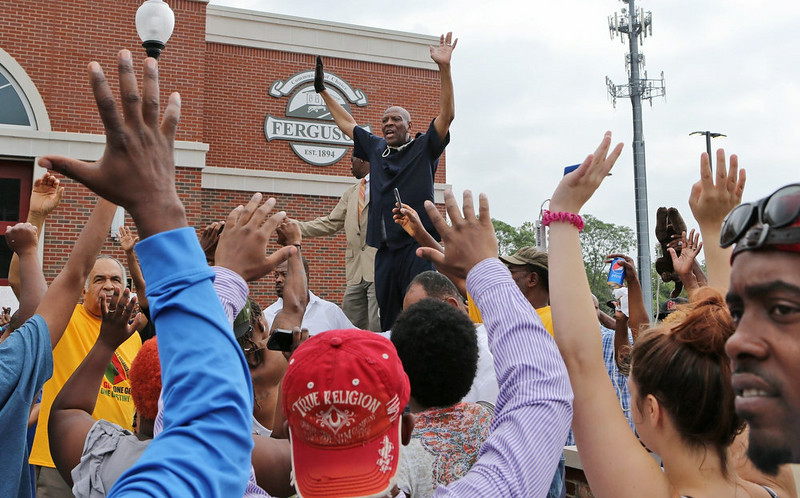 . Activist Anthony Shahid tells the crowd to put their hands up on Sunday morning, Aug. 10, 2014, in Ferguson, Mo., as part of the protest against the police shooting of Michael Brown on Saturday. (AP Photo/St. Louis Post-Dispatch, J.B. Forbes)