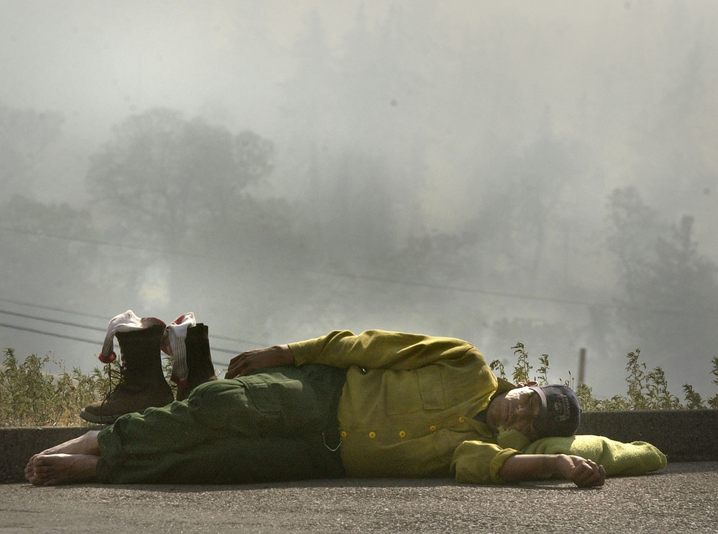 . Leotis Raye sleeps in a parking lot overlooking a smoldering hillside at Julian, Calif. Oct. 29, 2003. Raye, a firefighter for the Navajo Hotshots, was resting after spending 30 hours fighting the Cedar fire near San Diego. (AP Photo/Charlie Riedel)